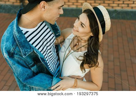 Happy Young Hipster Couple Looking At Each Other And Hugging On The Street