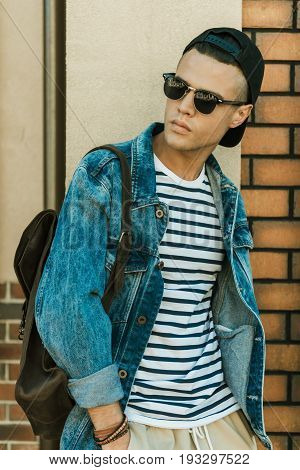 Stylish Young Man In Denim Jacket And Sunglasses Standing Outdoor