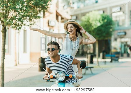 Handsome Man In Sunglasses And Happy Young Woman In Straw Hat Riding Moped And Smiling