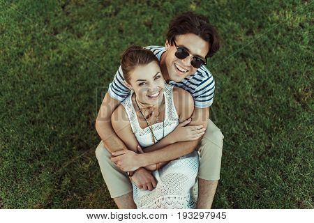 Young Smiling Sweethearts Hugging And Looking At Camera While Sitting On Grass