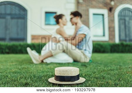Sweethearts Able To Kiss While Sitting On The Grass Outdoors, Selective Focus On Straw Hat