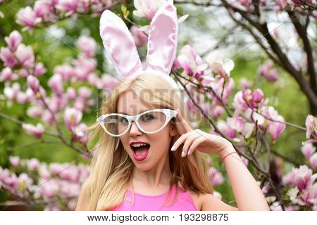 woman or cute girl with open mouth bunny ears and funny glasses with long blond hair at blossoming tree with magnolia flowers in spring park on floral environment. Easter. Springtime