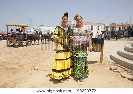 El Rocio Spain - June 2 2017: Female pilgrims in traditional flamenco dresses in El Rocio during the pilgrimage Romeria 2017. Province of Huelva Andalusia Spain