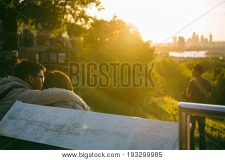 LONDON, UK - MAY 22, 2017: Couple sitting on the ground the top of the hill at Greenwich Park, London, hugging and watching sunset