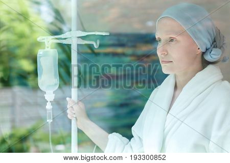 Young woman with drip standing by the window before operation