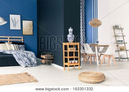 Stylish white and blue studio with wooden furniture