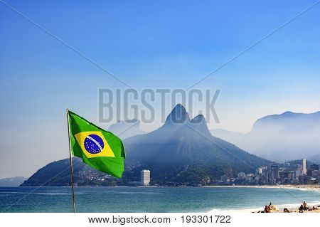 Brazilian flag at Ipanema beach in Rio de Janeiro with Two Brothers hill and Gavea stone in background