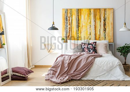 Yellow monochromatic painting above a big double bed