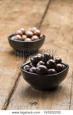 dark chocolate pralines into black bowl on wooden table