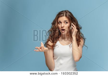 The portrait of disgusted woman with mobile phone on studio background