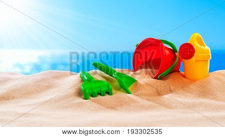 On the Beach - sand toys on a sand dune in front of beautiful azure sea on a sunny day