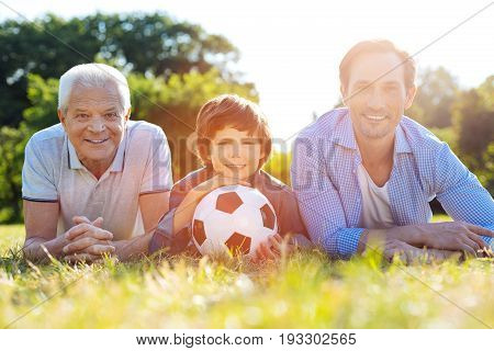 Continuity of life. Attractive active positive kid and his dad and grandpa enjoying nice weekend with his family while going in the park and playing football together