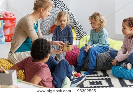 Group of little kids playing game in the circle in kindergarten
