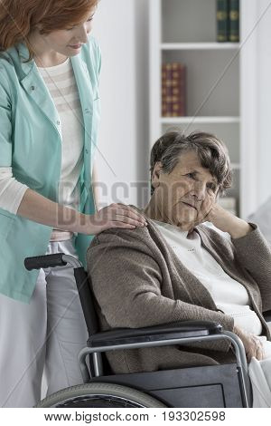 Sad old disabled lady in wheelchair feeling worse