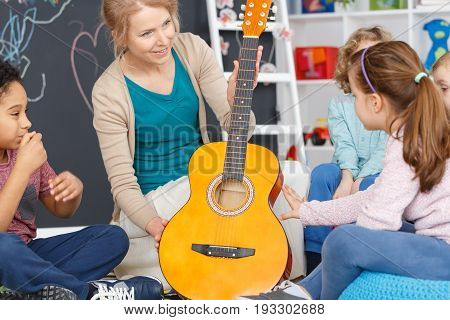 Kindergarten teacher during music classes with guitar for kids