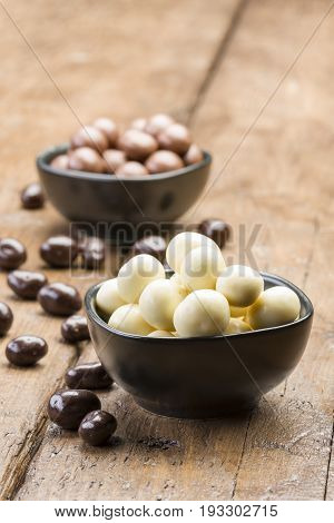 white chocolate pralines into black bowl on wooden table