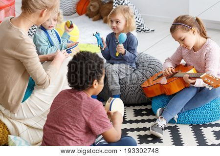 Group of little children playing music in kindergarten