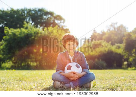 Energetic kid. Adventurous energetic handsome boy enjoying warm weather while going in the park and taking a ball for playing football