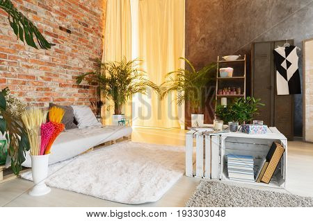 Hipster leisure room in decorated stylish industrial apartment with brick wall