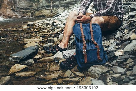 Unrecognizable Male Hiker Sits On River And Enjoys Surrounding View Exporing Adventure Hiking Concept