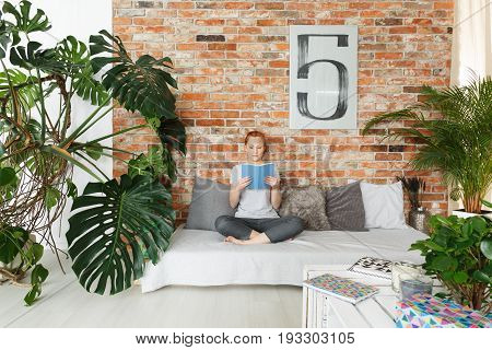 Young attractive woman reading book in stylish contemporary apartment