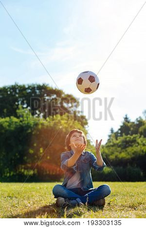 Never at rest. Imaginative dynamic lively kid throwing ball up in the air and catching it while sitting on the grass in the park