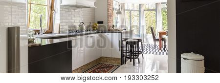 Functional small kitchen in the traditional style open to the bright dining room with large windows
