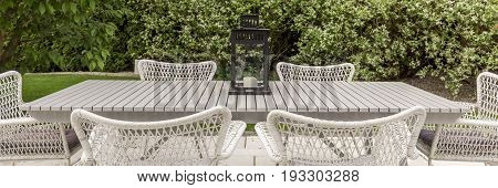 Terrace in the backyard garden with white patio chairs and table