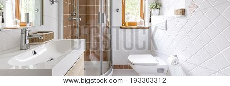 Small but functional bathroom in white with toilet sink and shower