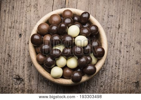 assorted chocolate pralines into wooden bowl on wooden table