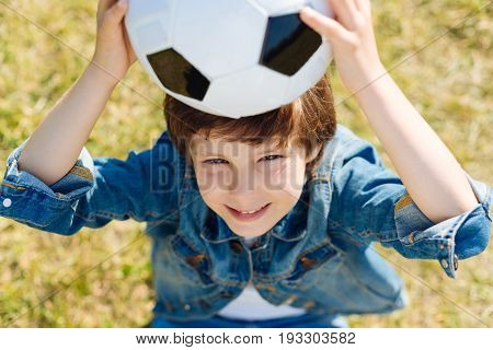 Got it. Motivated energetic admirable child having fun while sitting on the grass and taking a break from playing football