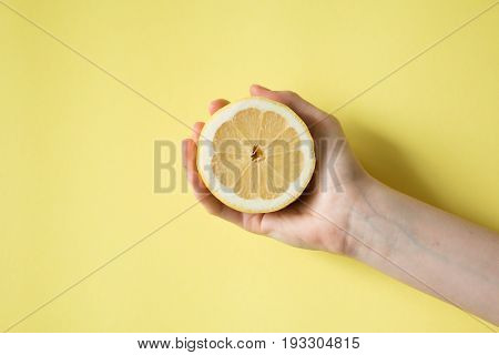Lemon In Woman's Hand On A Yellow Background