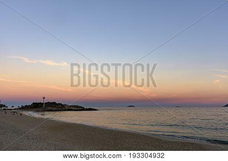 Landscape of Arpoador beach in Rio de Janeiro during dusk