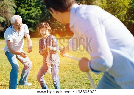 Believe in yourself. Intelligent supportive aged man giving his grandchild an advice while he playing with his dad and pulling the rope