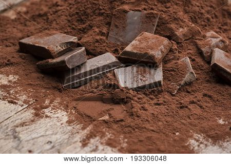 heap of cocoa powder with chocolate block on wooden table