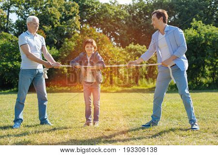Activity for strength. Elderly smart optimistic man, his son and grandson enjoying a nice weekend outside the city and enjoying active games while pulling a rope
