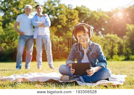 Technology everywhere. Vibrant charming clever boy having a picnic in a park and listening to some music while sitting on a grass and wearing headphones