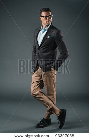 Stylish Man In Suit And Eyeglasses Looking Away Isolated On Grey