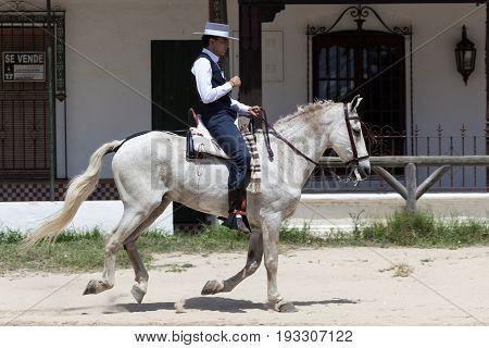 El Rocio Spain - June 2 2017: Pilgrim on horseback in traditional spanish dress in El Rocio during the Romeria 2017. Province of Huelva Almonte Andalusia Spain