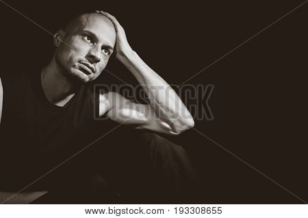 Depression. Depressed man sitting in the dark. Dark image. Dark background.