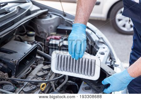 Auto mechanic wearing protective work gloves holds a dirty air filter over a car engine. Internal combustion engine air filter.