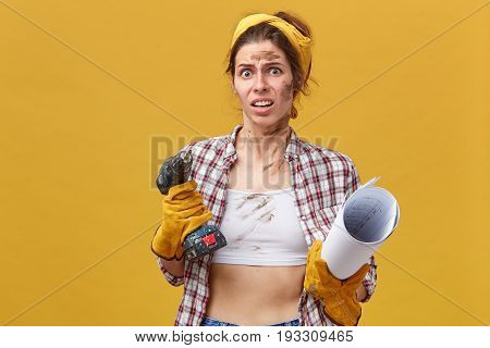 Portrait Of Young Female Electrical Technician Having Discontented Look After Hard Work Being Dirty