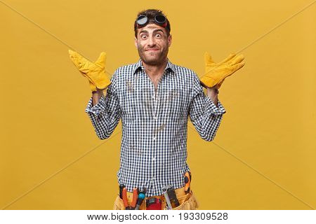 Young Handyman Wearing Protective Goggles And Gloves, Chekered Shirt Equipped With Working Instrumen