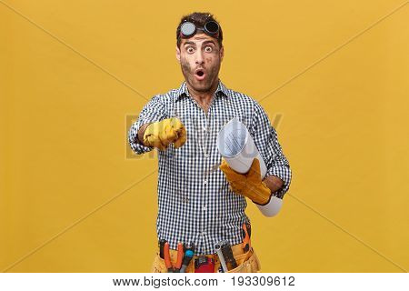Portrait Of Excited Male Plumber Wearing Protective Eyeglasses, Checkered Shirt, Belt With Instrumen