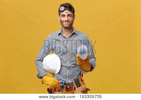 Pleased Dirty Man Worker Having Prootective Goggles On Head And Holding Rolled Paper With Hardhat Is