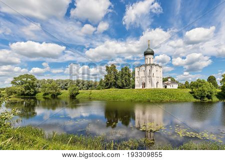 Church of the Intercession on the Nerl reflecting in water on sunny day with scenic clouds in Bogolubovo Vladimir oblast Russia