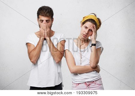Studio Portrait Of Unhappy Depressed Young Couple Feeling Stressed, Facing Financial Problems Or Hav