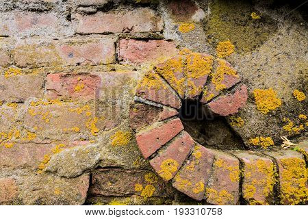 Weathered red bricks are decoratively situated in wall
