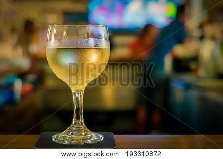A glass of white wine ready for sampling.