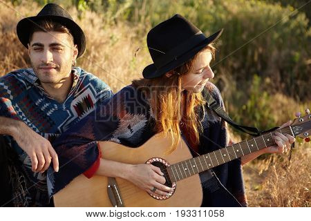 Talented Female Model Wearing Black Hat Holding Guitar Playing It And Singing Songs While Sitting Ne